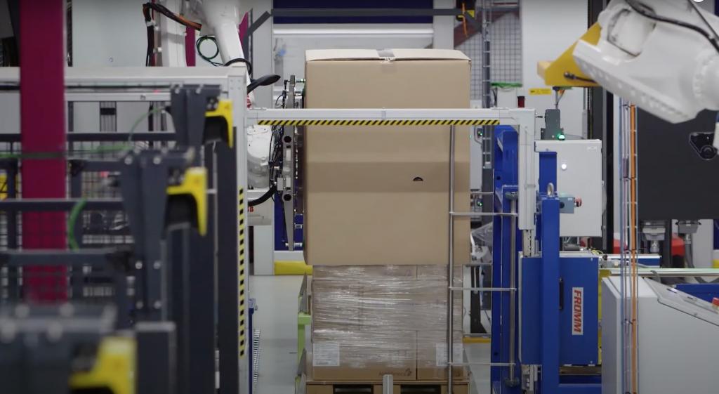 Nasadenie kartónového obalu priemyselným robotom